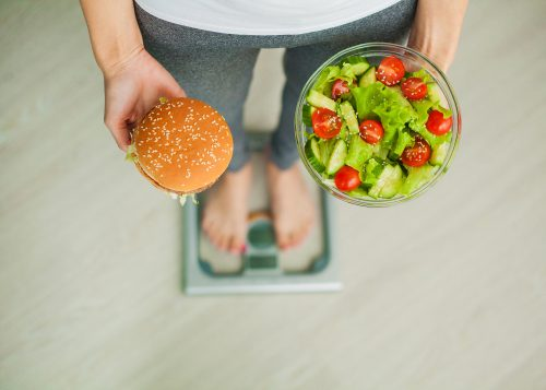 Diet. Woman Measuring Body Weight On Weighing Scale Holding Burger and Salad. Sweets Are Unhealthy Junk Food. Dieting, Healthy Eating, Lifestyle. Weight Loss. Obesity. Top View.